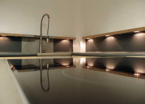 Küche - Ahorn, Beton und Linoleum; Im massiven Holzsims sind Steckdosen, Schalter und speziell entworfene, verstellbare Leuchten aus Edelstahl eingelassen. Ansicht beleuchtete Arbeitsfläche;