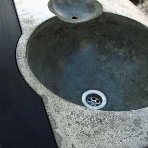 Detail Badezimmerwaschbecken, mit eingegossenem Überlauf, Seifenschale und Ablagen; Verschiedentlich pigmentierter Betonguss, stahldraht- und glasfaser-verstärkt, geölt und imprägniert;