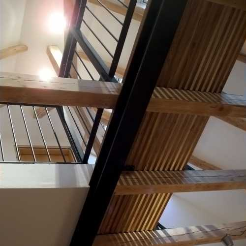 Treppe, Verbindungssteg und Galerie - lackierter Stahl und geöltes Eichenholz; leichte Konstruktion aus Eichenleisten mit lebhaftem Licht- und Schattenspiel;