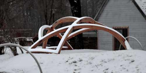 Lärchenholzkuppel aus gebogenen Leimbindern für den Spielplatz im (link: http://www.zoo-hof.de/ text: Zoo Hof); Sie spannt sich mit einem Durchmesser von etwas über sechs Metern über eine Vertiefung, in der sich fünf eingegrabene Kriechröhren (der